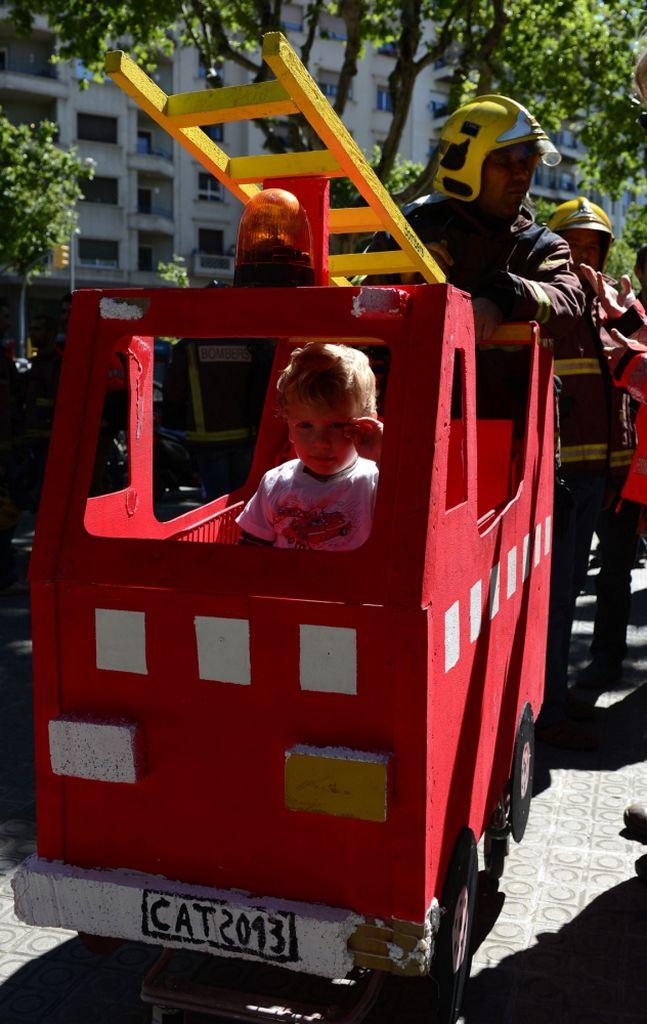 Ян, двухлетний ребёнок пожарного изображает папу на пожарной машине на фоне парламента Каталонии во время демонстрации против урезания расходов на социальные службы.